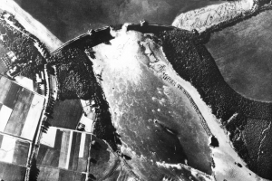 Aerial reconnaissance photograph taken on 17 May 1943 showing the breach in the Mohne Dam caused by 617 Squadron\'s raid during the previous night. The Eder Dam was breached by means of \'bouncing bombs\' designed by Barnes Wallis. This spectacular feat of precision bombing had tremendous propaganda value, although its practical effects were less great than many had hoped © Crown Copyright