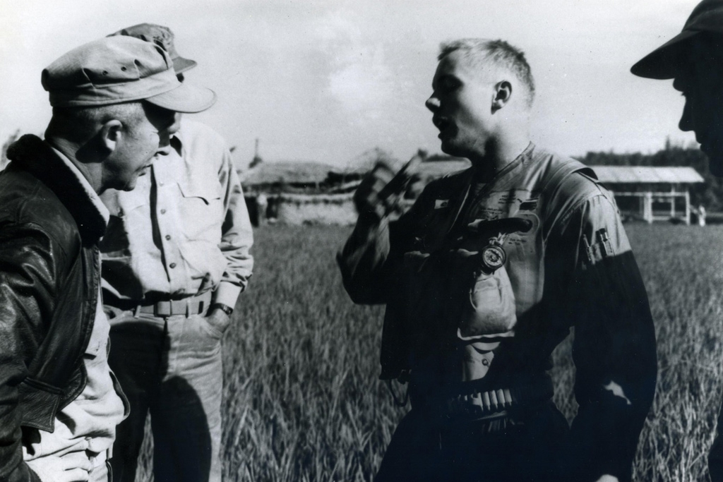 After bailing out of his Grumman Panther over Pohang Airfield in September 1951, Neil Armstrong, still holding the D-ring from his ripcord, chats with local Marines, including an old friend from flight school! US Navy / Public Domain