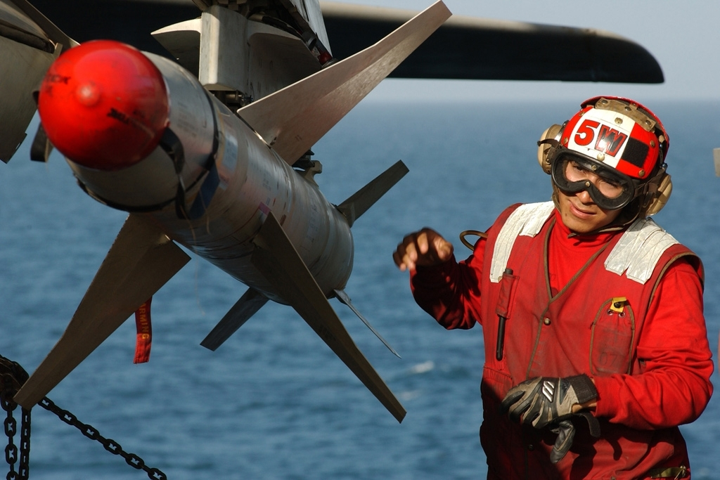 Airman Francisco Escobedo, assigned to the Gauntlets of Electronic Attack Squadron One Thirty Six (VAQ-136), prepares a High Speed Anti-Radiation Missile (HARM) on an EA-6B Prowler on the flight deck aboard the aircraft carrier USS Kitty Hawk (CV 63) - U.S. Navy photo by Photographers Mate 3rd Class Todd Frantom